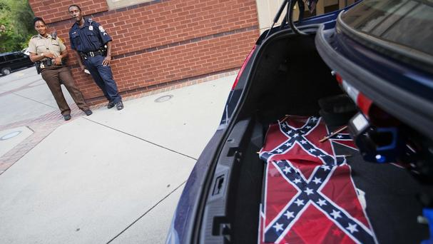 Confederate flags sit in the back of a police car outside Ebenezer Baptist Church. (AP)