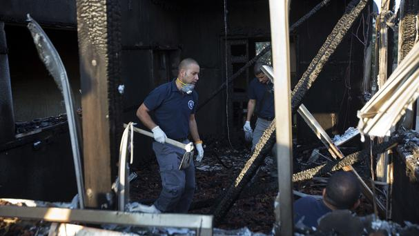 Israeli policemen inspect a house after it was torched in a suspected attack by Jewish settlers killing an 18-month-old Palestinian child (AP)