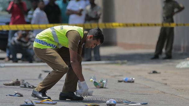A police officer inspects the site of a gun attack in Colombo, Sri Lanka (AP)