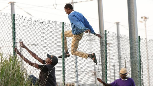 Migrants climb over a fence on to the tracks near the Eurotunnel site at Coquelles in Calais