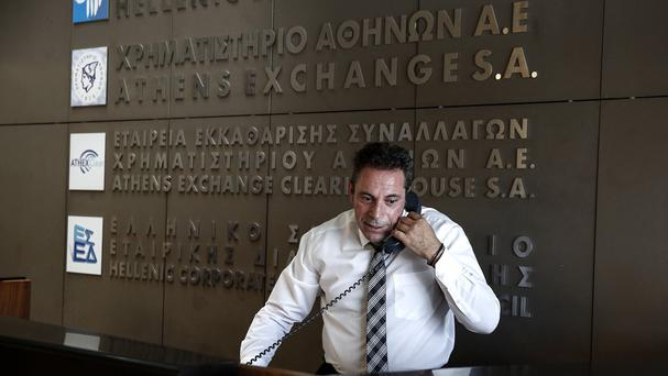An employee of the Athens Stock Exchange speaks on the phone in the reception hall in Athens (AP)