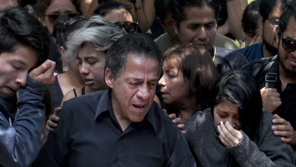 A family member of murdered photojournalist Ruben Espinosa says his last goodbye during his funeral service in Mexico City (AP)