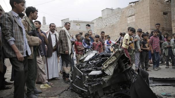 People stand amid wreckage of a vehicle at the site of a car bomb attack next to a Shiite mosque in Sanaa, Yemen (AP)