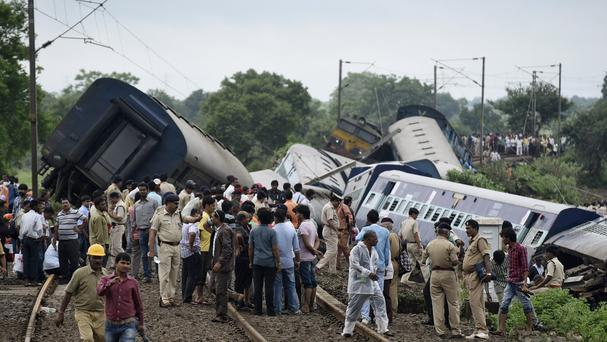 People gather at the site of a train accident near the town of Harda in Madhya Pradesh state, India (AP)