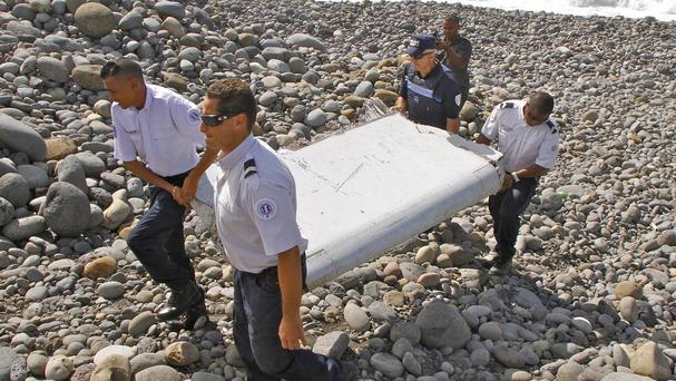 French police officers carry the wing debris found on Reunion Island (AP)
