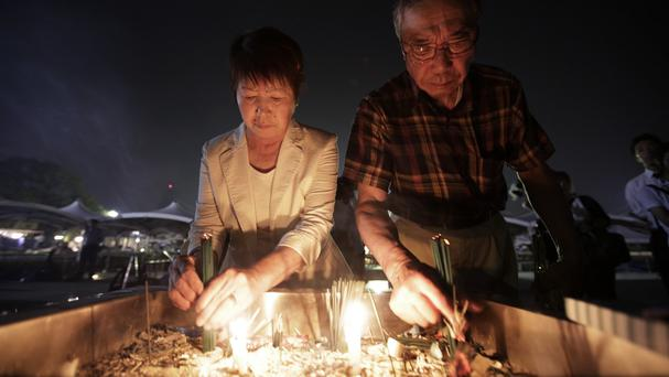 People burn joss sticks in front of the cenotaph for the atomic bombing victims in Hiroshima (AP)