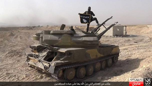 An IS militant holds the group's flag as he stands on a tank captured from Syrian government forces, in the town of Qaryatain, Syria (Rased News Network, a Facebook page affiliated with Islamic State militants, via AP)