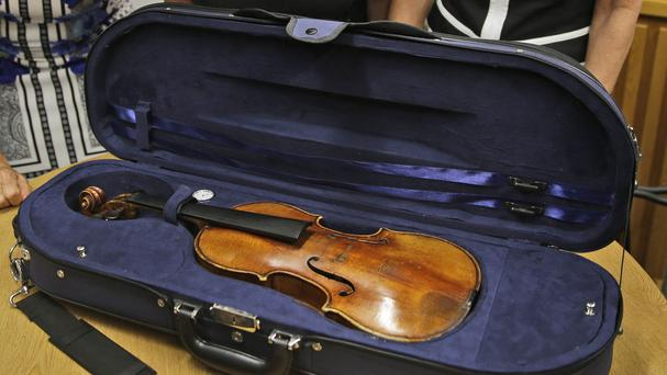 Sisters Amy Totenberg, left, Nina Totenberg and Jill Totenberg examine the Stradivarius violin (AP)