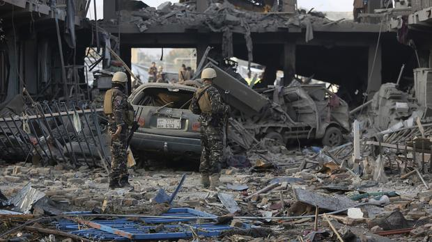 Afghan security personnel inspect the site of a truck bomb attack in Kabul (AP)