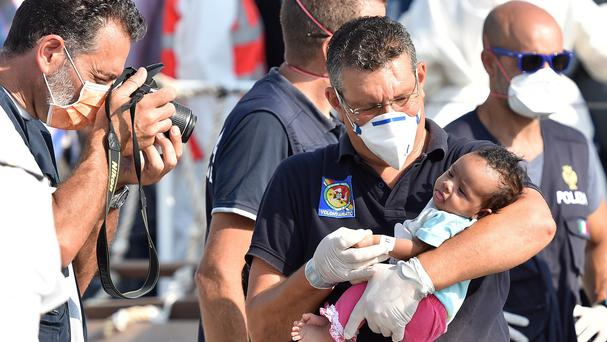 Italian officers help migrants disembarking from an Italian coastguard ship in Sicily. (AP)