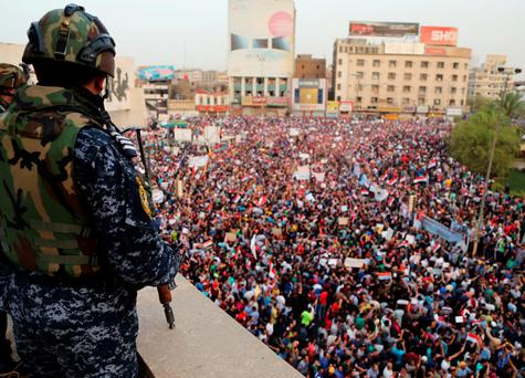 An Iraqi federal police officer watches as protesters chant anti-government slogans in Tahrir Square, Baghdad, on Friday