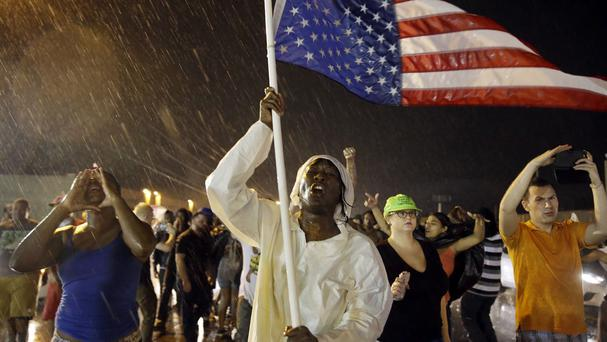 Protesters march in the rain in Ferguson, Missouri, one year since Michael Brown was shot and killed (AP)