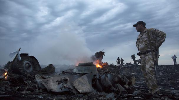 People walk amongst the debris at the crash site of a passenger plane near the village of Grabovo, Ukraine (AP)
