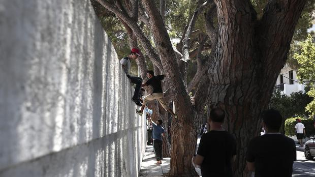 A migrant tries to climb a wall to enter a stadium on Kos (AP)