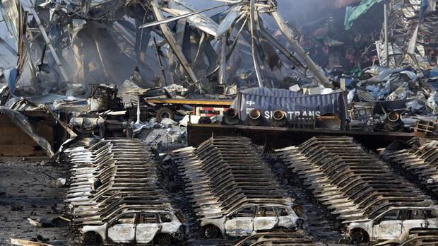 Charred remains of a warehouse and new cars are left burned after an explosion at a warehouse in China's Tianjin municipality (AP)
