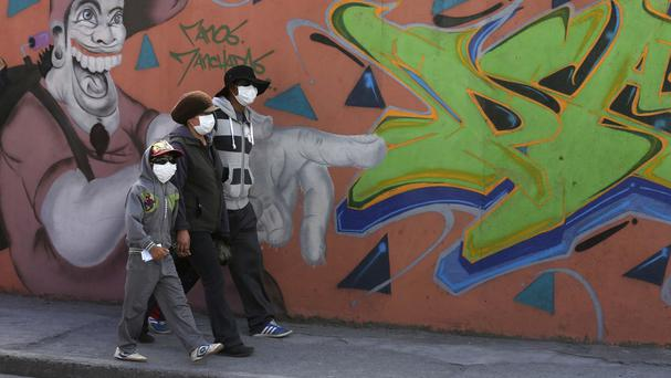 Residents wear masks to protect themselves from volcanic ash spewed from Cotopaxi volcano. (AP)