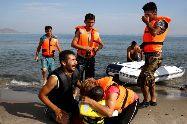 An Iranian migrant cries next to his son and wife moments after making land in Kos