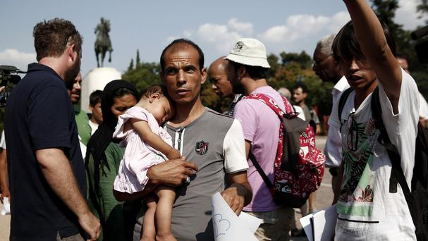 Migrants wait to be transferred from an Athens park to an organised camp (AP)