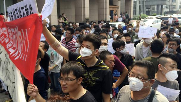 Demonstrators protest outside a hotel where officials held daily media conferences in north eastern China's Tianjin municipality. (AP)
