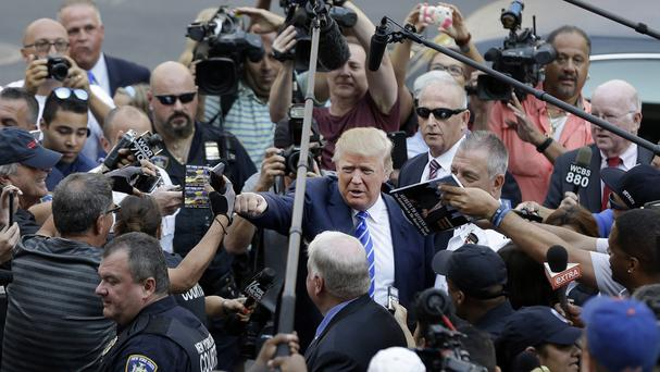 Donald Trump gives a fist bump to a pedestrian as he arrives for jury duty in New York (AP)