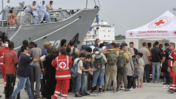Migrants disembark from the Croatian Coast Guard ship SB72 Andrija Mohorovicic at Augusta harbour, near Siracusa, Sicily (AP)