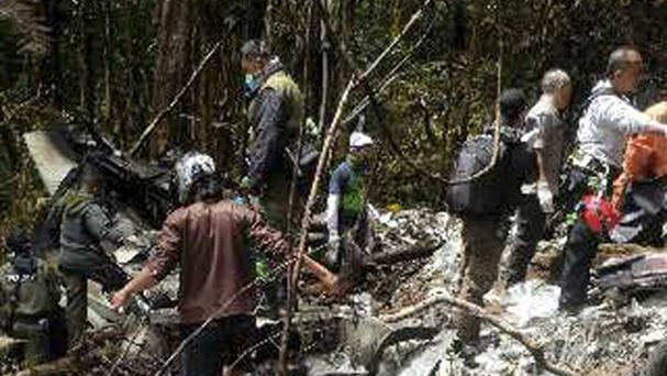Officials and rescue workers gather by plane wreckage strewn across dense terrain in a remote area of Pegunungan Bintang, Papua province, Indonesia. (AP)