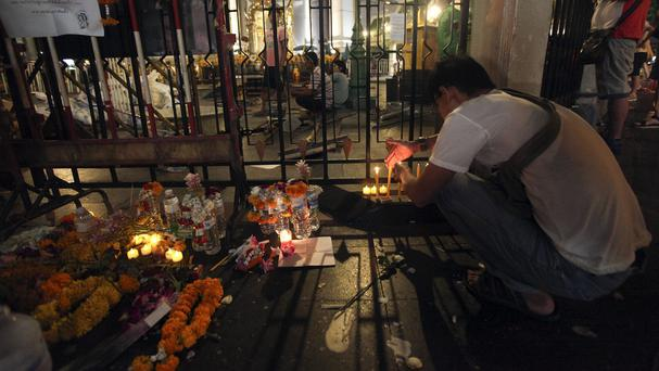 A man lights candles near Erawan Shrine in Bangkok (AP)