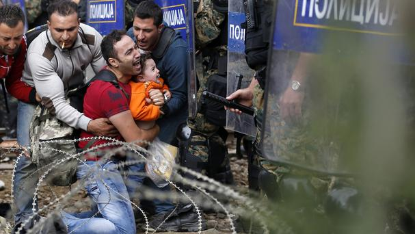 A migrant holds a boy as they are stuck between Macedonian riot police officers and migrants during a clash near the border train station of Idomeni, northern Greece (AP)