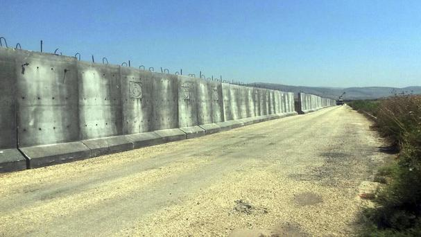 Part of a wall under construction is seen along the border with Syria in the town of Reyhanli in Hatay province, Turkey (AP/DHA)