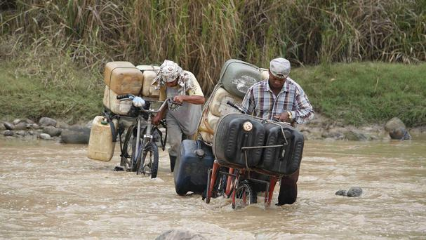 Smugglers cross the Tachira River carrying Venezuela petrol into Colombia, in Cucuta, at the border with Venezuela, in 2008 (AP)