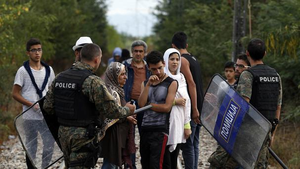 Macedonian police officers speak with migrants after entering into Macedonia from Greece. (AP)
