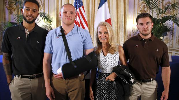 (l to r) Anthony Sadler, Spencer Stone, Jane D. Hartley, US Ambassador to France, and Alek Skarlatos pose for photographers (AP)
