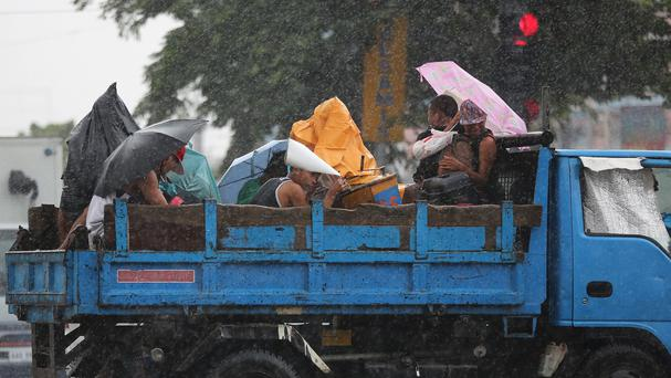 Filipinos riding on a truck take cover during rain from a monsoon that hit Manila and other parts of Asia