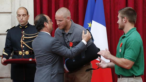 French president Francois Hollande kisses US airman Spencer Stone, while Alek Skarlatos applauds after they were awarded the Legion of Honour in Paris (AP)