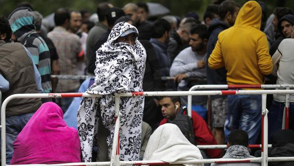 Migrants wait for registration at a reception centre for refugees and asylum seekers. (AP)