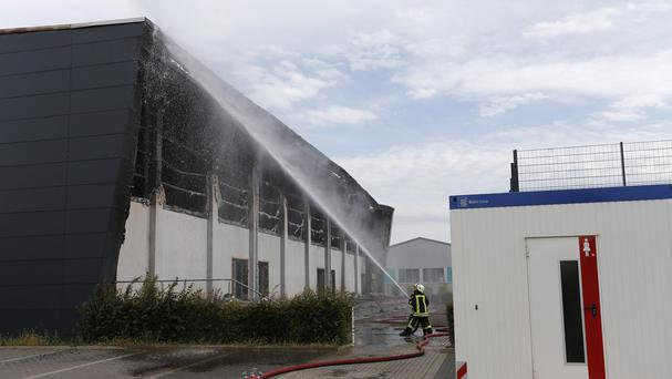 Firefighters tackle the blaze at a gym intended as temporary housing for refugees in Nauen, west of Berlin. (AP)