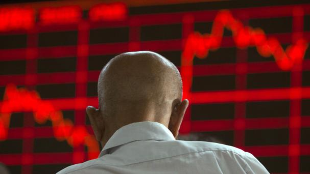 A Chinese investor monitors stock prices at a brokerage in Beijing (AP)