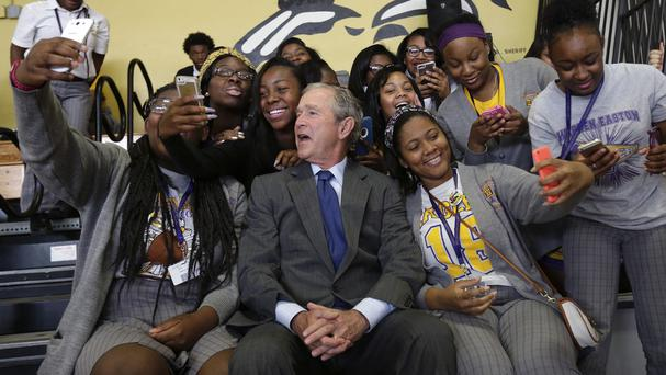 Former US president George W. Bush poses for photos with students at Warren Easton Charter High School in New Orleans. (AP)