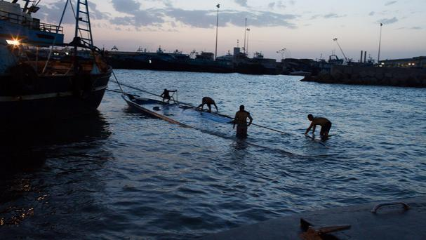 A sunken boat carrying migrants is pulled in to the port Zuwara, Libya. (AP)