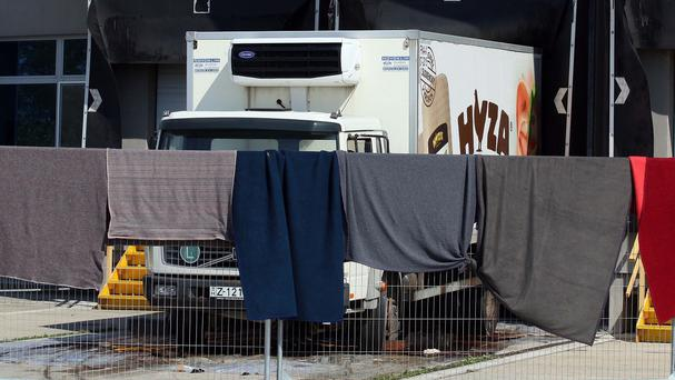 Blankets block the view of a truck that was found to have the bodies of 71 migrants in Austria (AP)