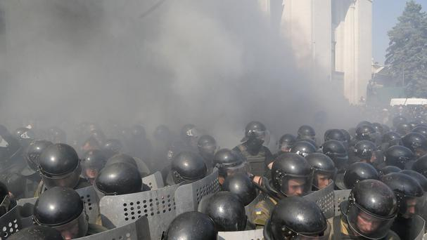 Smoke rises from outside the parliament building as riot police clash with protesters