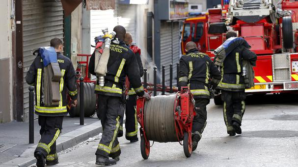 Rescue workers outside an apartment where eight people died in a fire (AP)