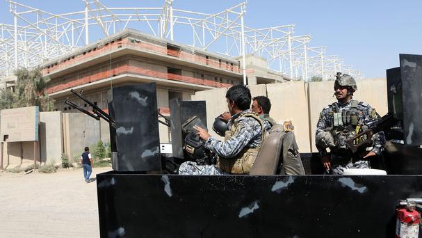 Iraqi security forces guard the entrance to the sports complex being built by a Turkish construction company (AP)