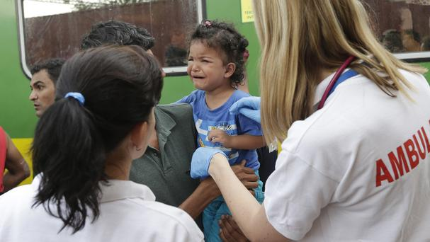 Medical staff treat a small child outside a train with migrants that was stopped in Bicske, Hungary (AP)