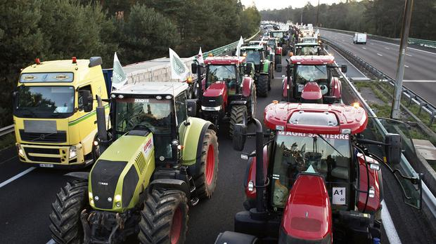 Farmers drive their tractors on a highway leading to Paris to join a protest over falling French food prices and high taxes (AP)