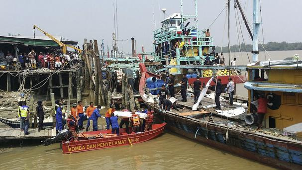 A rescue team unload the body of a victim retrieved near the area where a boat carrying Indonesian migrants sank off the coast of Malaysia (Malaysian Maritime Enforcement Agency/AP)
