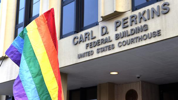 A protester waives a rainbow flag outside the Carl D Perkins Federal Building in Ashland, Kentucky. (AP)