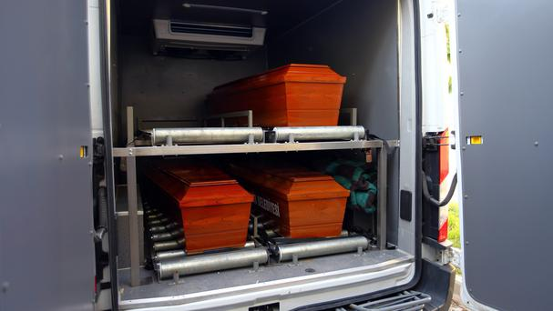 The coffins of dead migrants are placed in a hearse (AP)