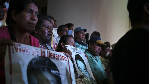 Parents of the 43 college students hold up images of their missing sons as they listen in to a press conference in Mexico City (AP)