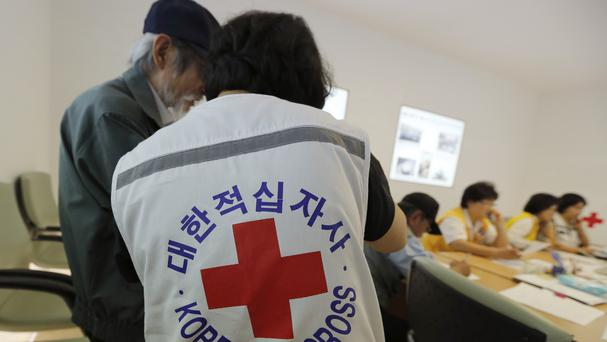 A South Korean man who was separated from his family during the Korean War is helped by a Red Cross member. (AP)
